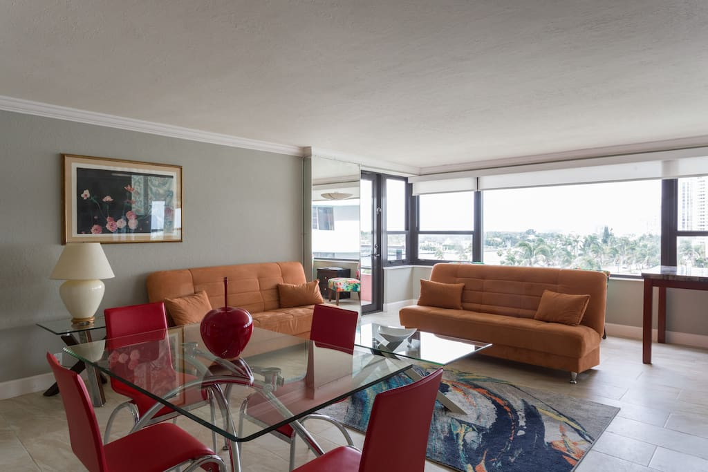 This is the living room and dining area.  There are motorized shades in this room  and impact windows in the entire apartment.  The orange futons are available for sleeping if needed