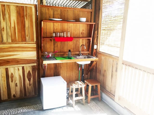 Small kitchen, features refrigerator, sink coffee maker and basic utensils.