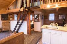 The queen bed is located  in the cozy nook  and the stairs lead to the king in the open loft.