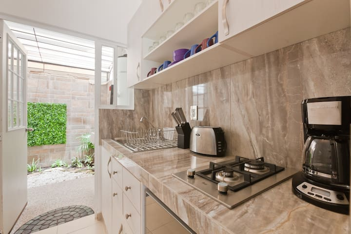 The kitchen, fully equiped including coffee machine(coffee & tea complimentary for you to enjoy!), toaster, microwave, stove and all necessary utensils. It has a direct access to the gorgeous back patio.