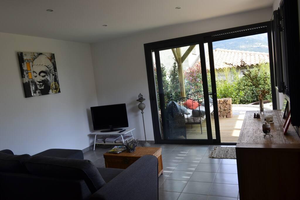 Appartement de plain pied avec ouverture sur terrasse en bois abritée.
