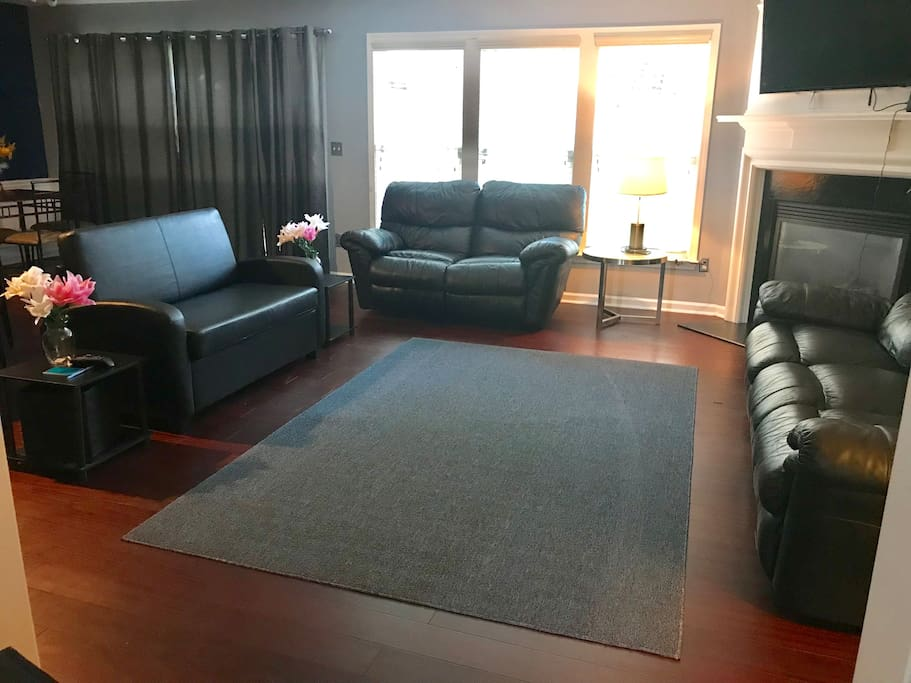 Living room hardwood floors & black leather furniture. One love seat is a twin pullout bed!