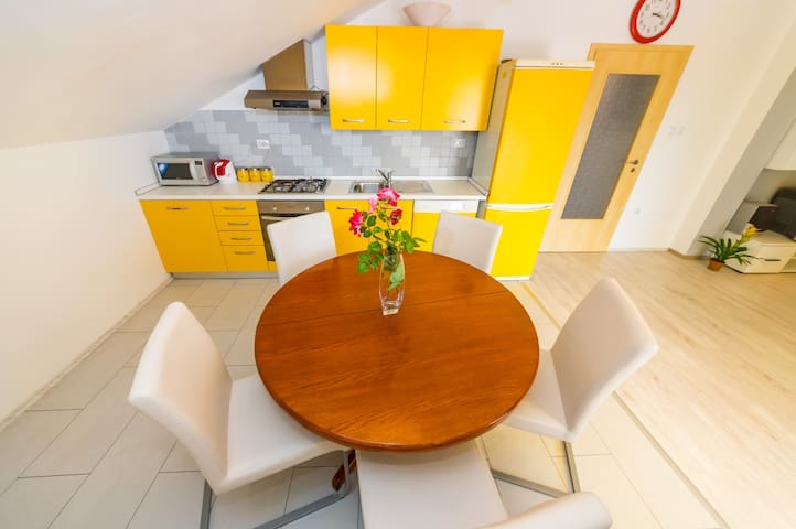 Dining room with kitchen: there is adjustable table (this is a smaller version), microwave, a kettle, electric oven, fridge, freezer, kitchen accessories and the dish washer