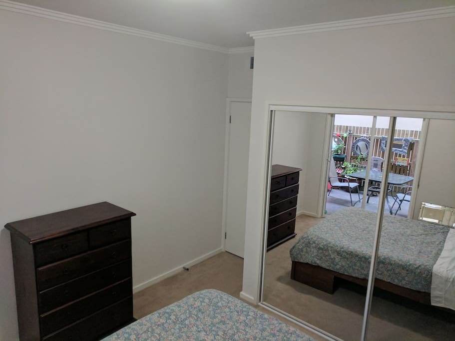 Spacious bedroom with tallboy for luggage storage.