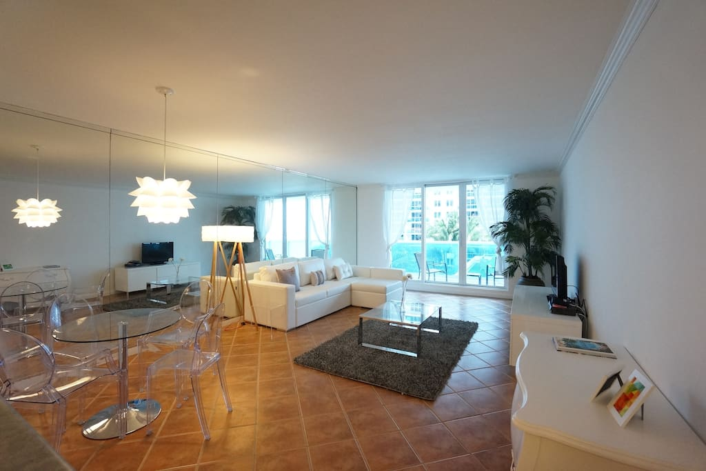 Living room with ocean view reflected in the mirrors and queen sofa bed