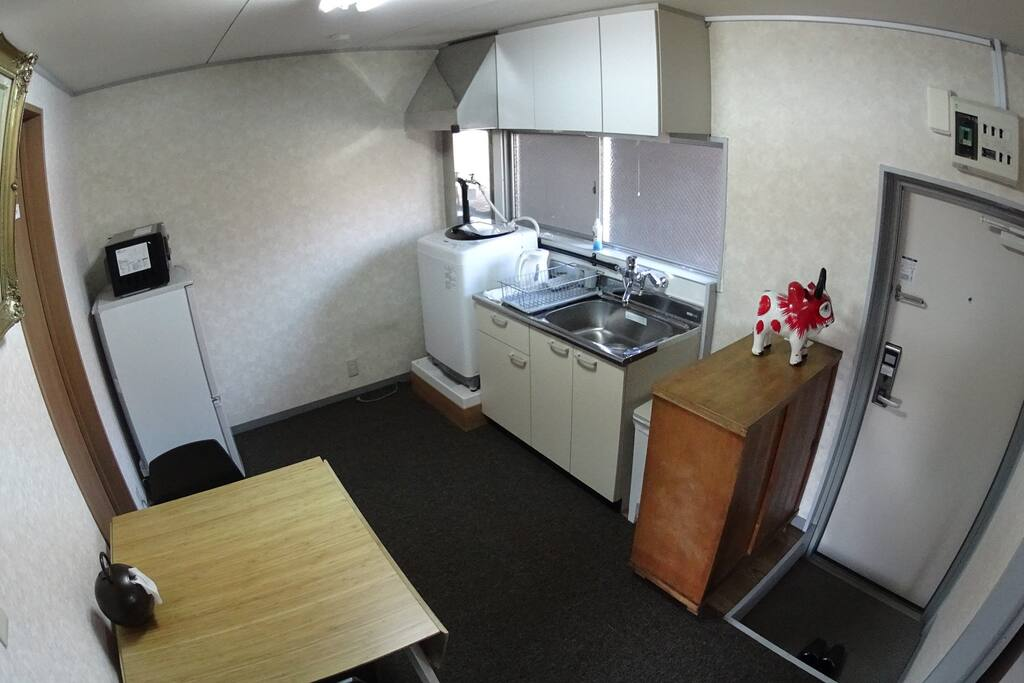 Kitchen with a microwave, a fridge, a kitcinette, and a laundry machine. A bamboo table is good for a small party.