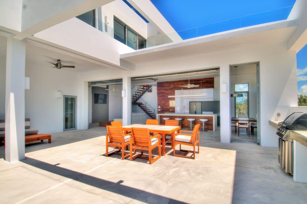 2 huge garage doors open up to create a wide, open, indoor/outdoor living space