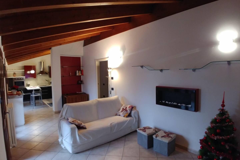 Luminoso salotto con divano, tv e caminetto bioetanolo