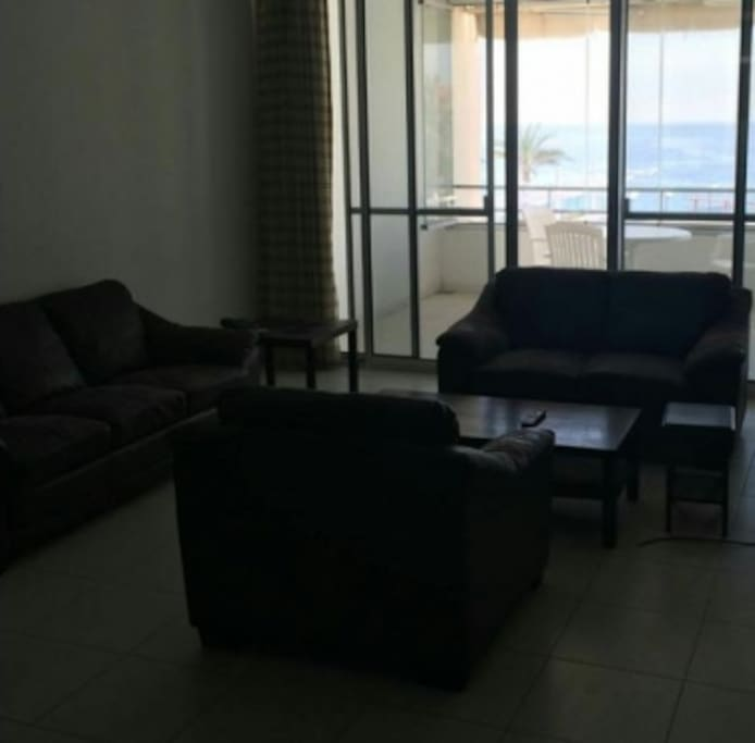 large living room with flat screen TV and convertible sofa;  open on a terrace
