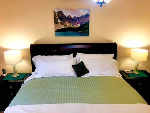 Banff Suite Premium King Bed featuring locally sourced Maple Hardwood Floors & matching Dark Cherry End Tables with Crystal Bed Lamps