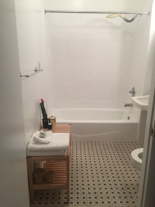 Clean white bathroom with bathtub and shower. Vanity amenities too for your stay !