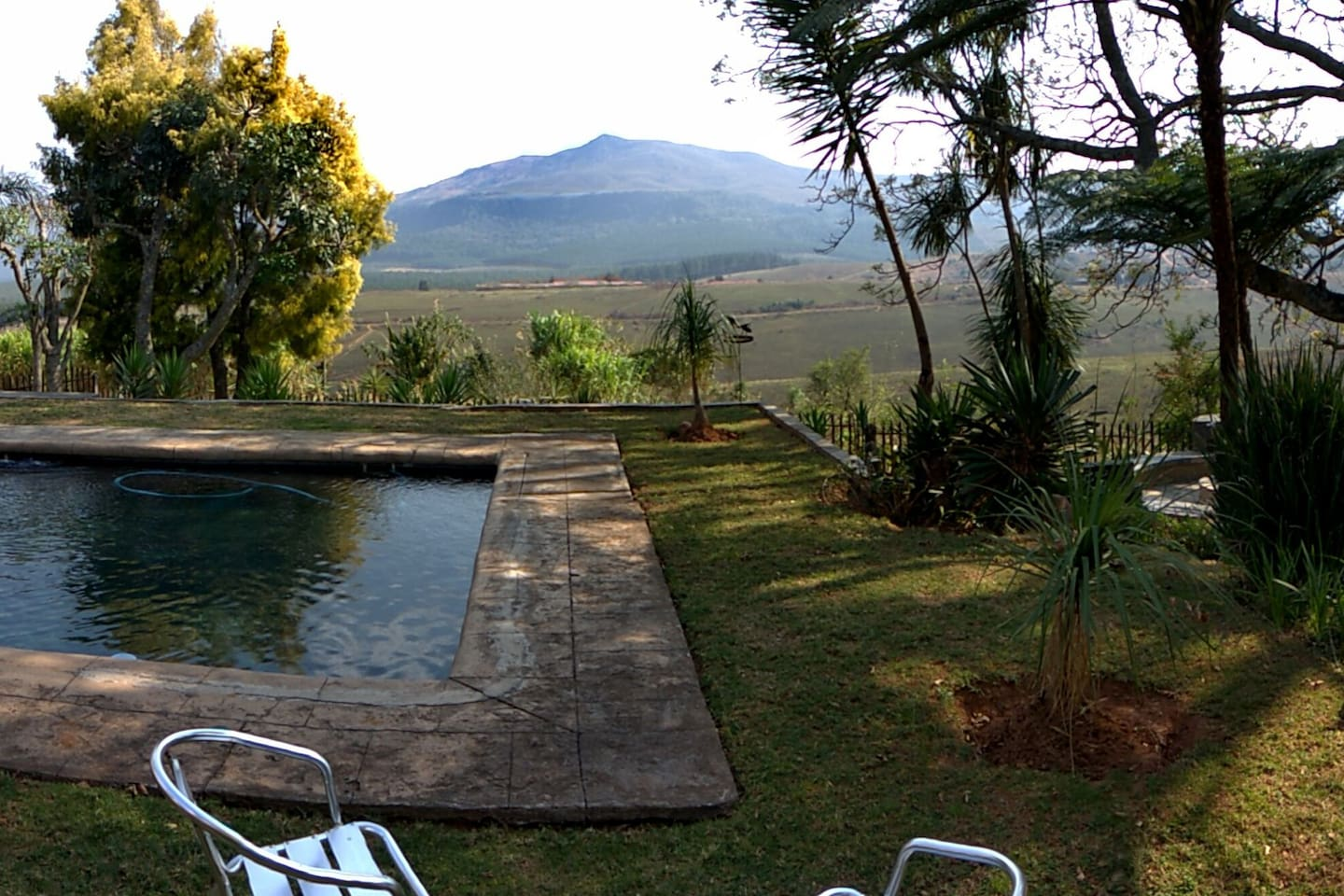 View across the valey of the mountain range, showing a section of the garden and pool.
