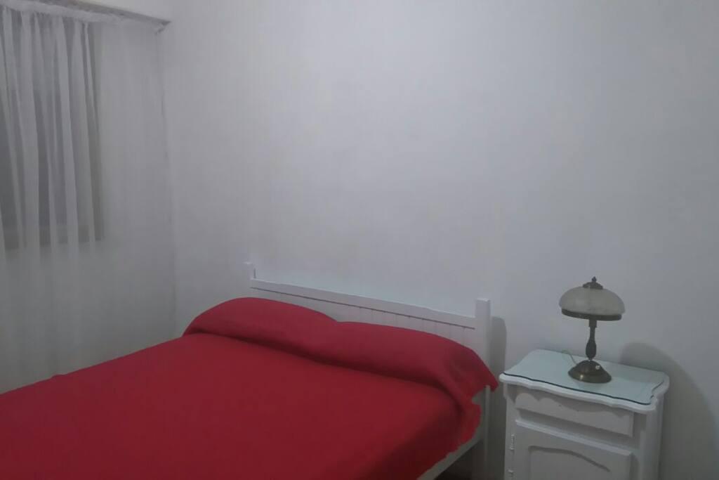 Dormitorio con cama de dos plazas, ventana hacia calle Alsina, amplio placard, calefactor, mesa de luz y cómoda