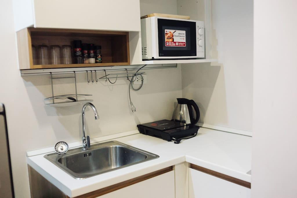 There is a fully functional kitchen with a stove, microwave, rice cooker (located under the sink), Coffee pot, and dish rack to help you dry all your dishes.