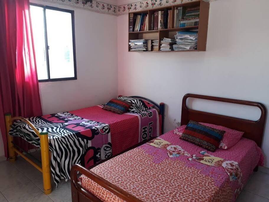 esta habitación tiene dos camas individuales y cuenta con armario su a abanico