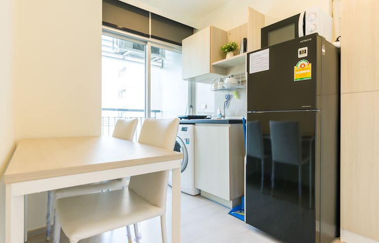 Chic kitchen and dining table with microwave, kettle, refrigerator, induction stove, kitchen utensils, washer and clothes line at balcony.
