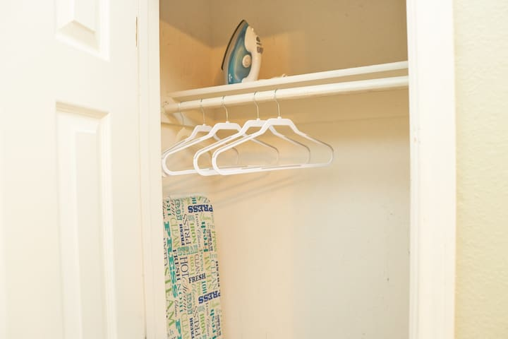 cloth hanger, iron and ironing board in closet