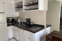Full kitchen with fridge, microwave, two burner stove, coffee maker, dishwasher, cooking utensils, plates, glasses, and flatware