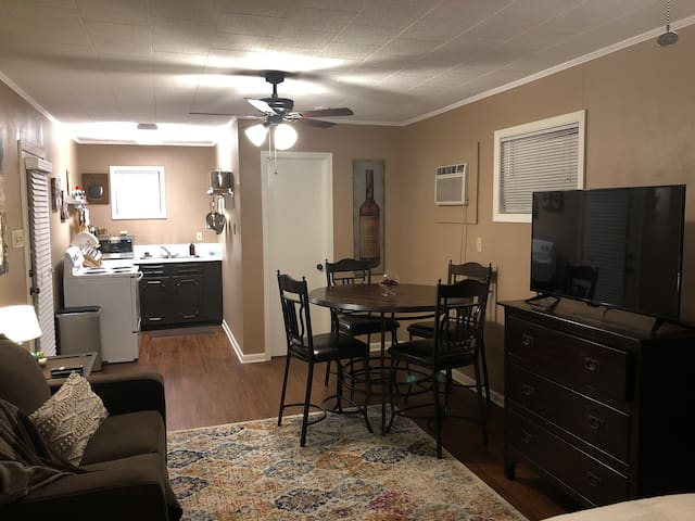 Table with 4 chairs, full kitchen on the left, and bathroom on the right