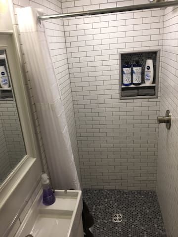 Here's the shower of the private bathroom. Guests can expect shampoo, conditioner, liquid soap, and washcloths. We also stock toiletries under the sink, including toothpaste, tooth brushes, Q-tips, and other essentials that guests may have forgotten.