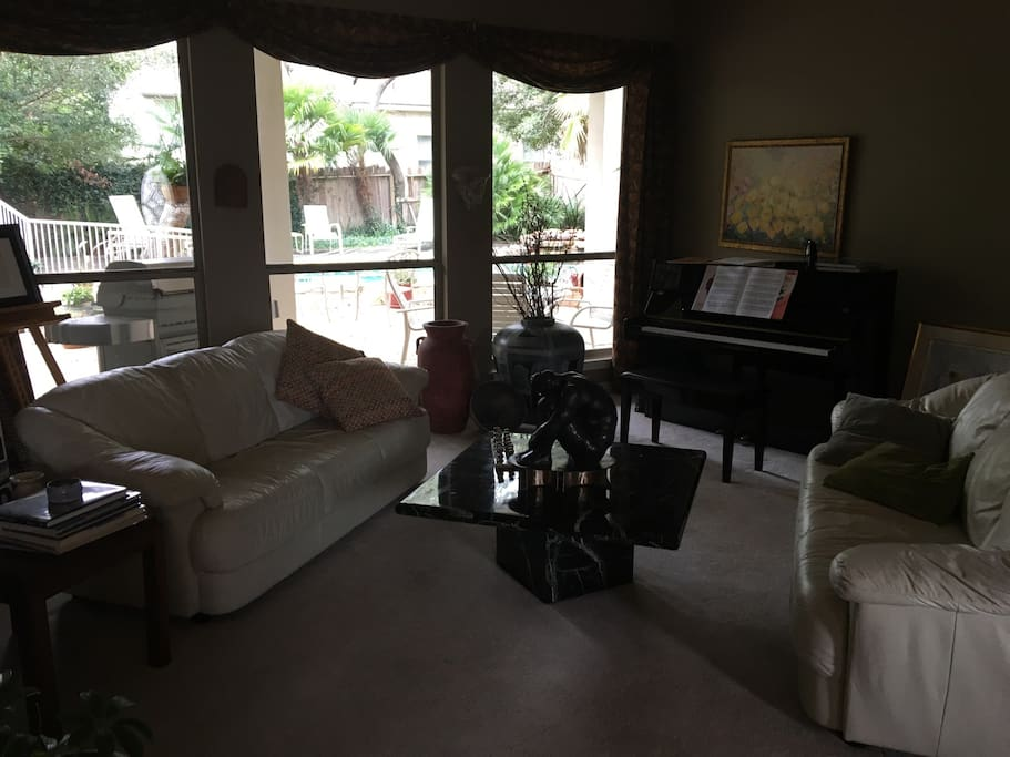 The living room overlooks the pool through wall-to-wall windows, flooding the space with natural lighting. This open room is a nice place to play cards, chess, or even the piano if you're a musician! It's also just a nice place to curl up and read a book with a hot cup of coffee.