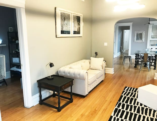 Bright, sun filled comfortable living room  with beautiful picture window to a quiet tree lined street. Outlets updated to usb options throughout unit