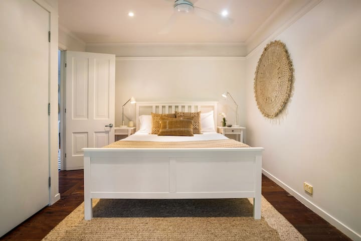 An elegant master bedroom is furnished with luxe black-out blinds and a plush queen bed topped with comfortable linen
