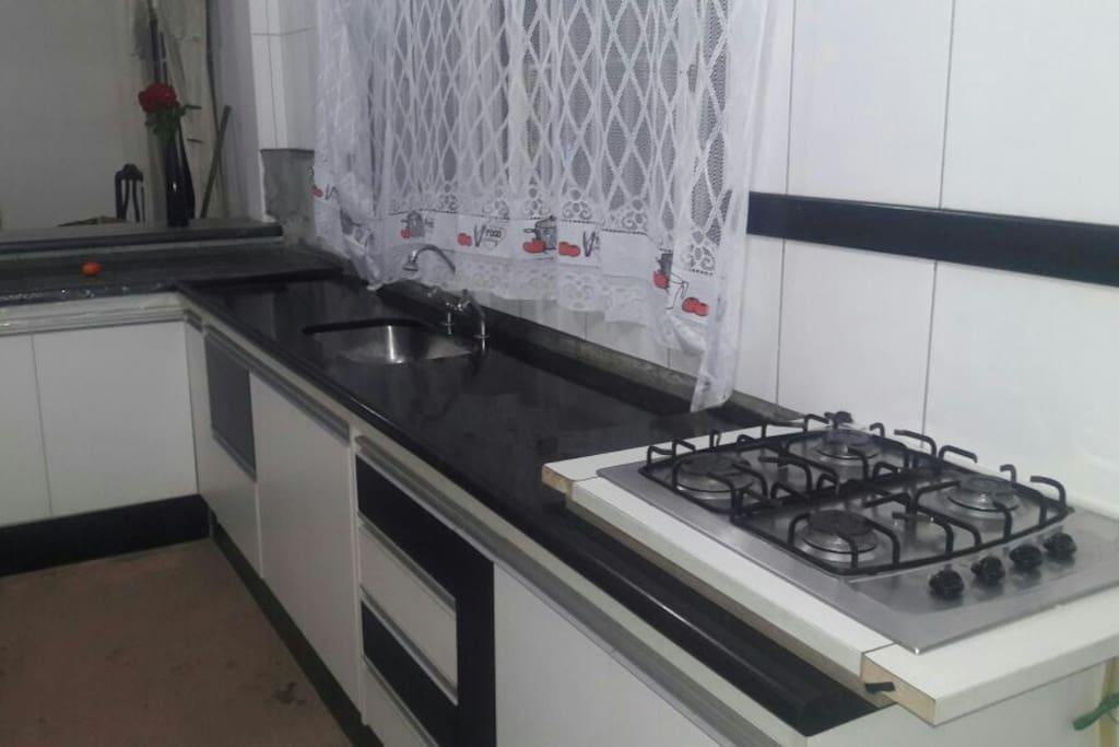 cozinha com balcão americano, pia ampla, fogão,  armários embutidos, talheres, panelas, grill. forno elétrico, balcão marmorizado preto, fogão coocktop.
