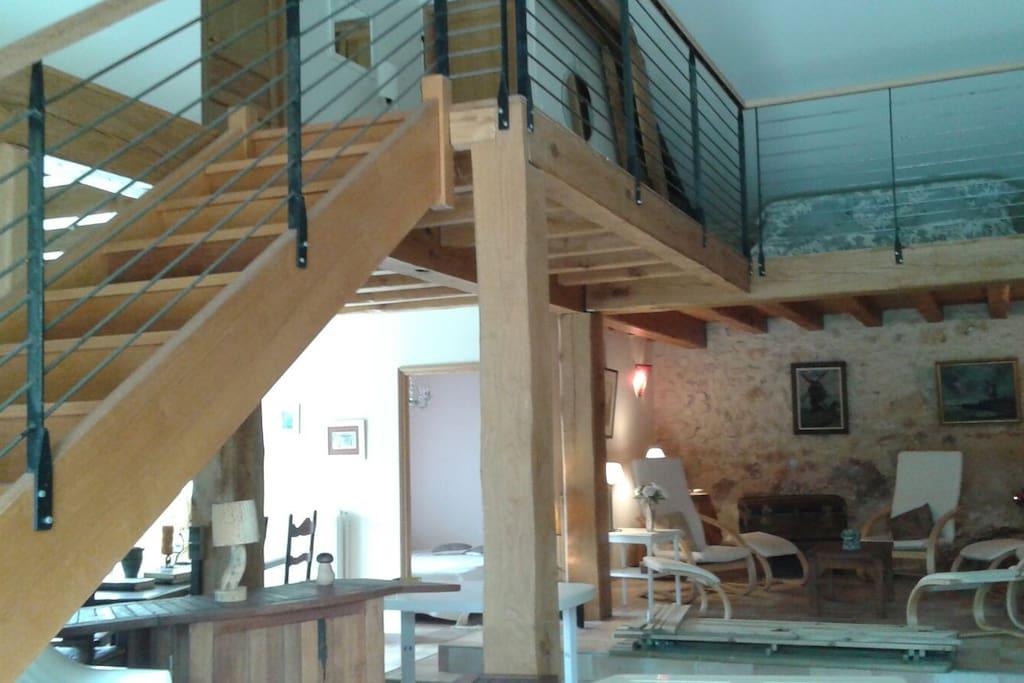 Immense cuisine ouverte, salon d'été et escalier donnant sur la mezzanine et les deux chambres du haut