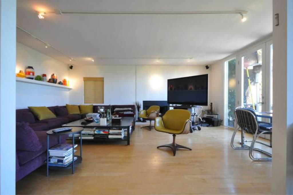 """The living room houses a stunning sectional sofa, a gaming table and a 65"""" professional plasma TV."""