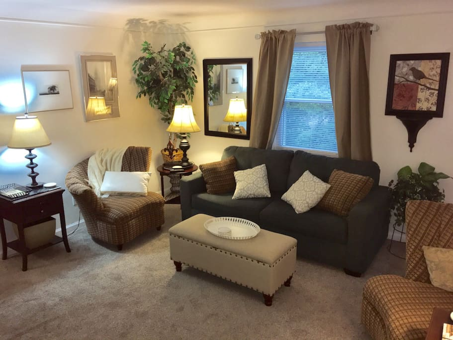 """Very spacious living room with a queen sofa bed.  Features a 50""""smart tv.  This area opens up to a small deck w/seating for 2."""