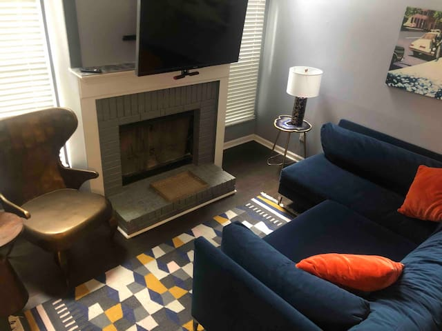 """Living space with 43"""" smart TV on adjustable mount over working gas fireplace."""