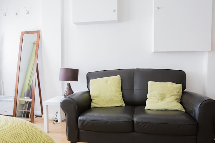 Comfy sofa for relaxing, full length mirror and coffee table.