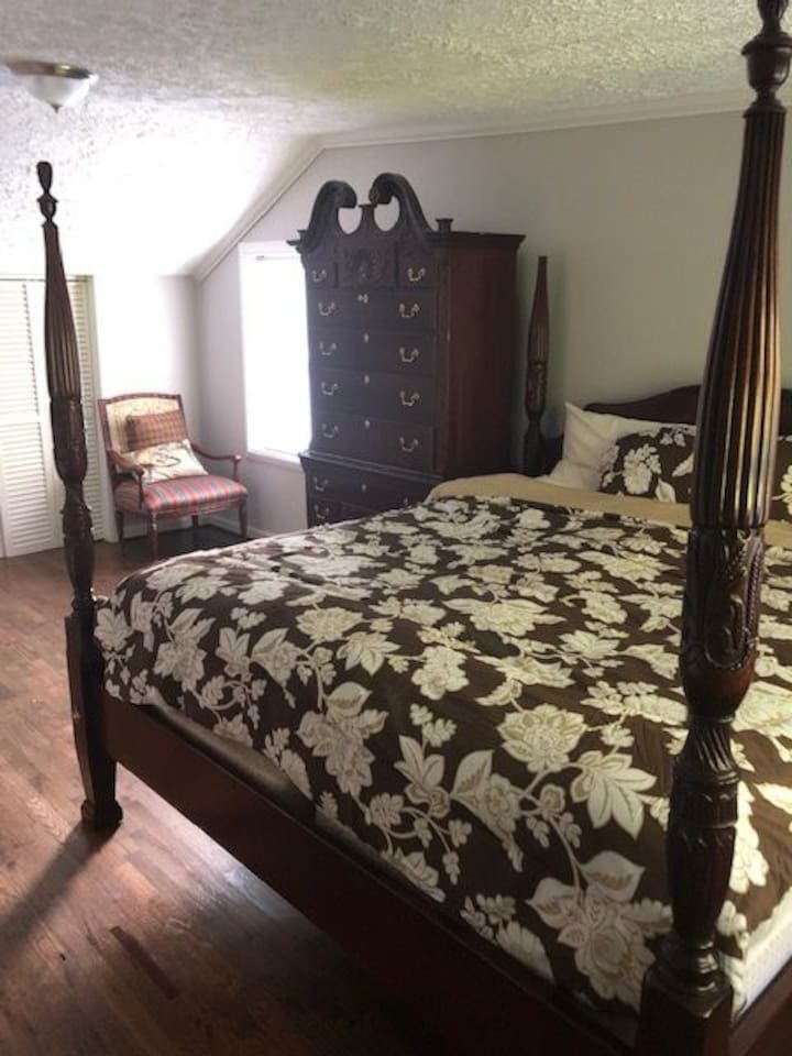 Large bedroom with tons of sunlight, king size bed, closet, tall dresser, and a full body mirror.