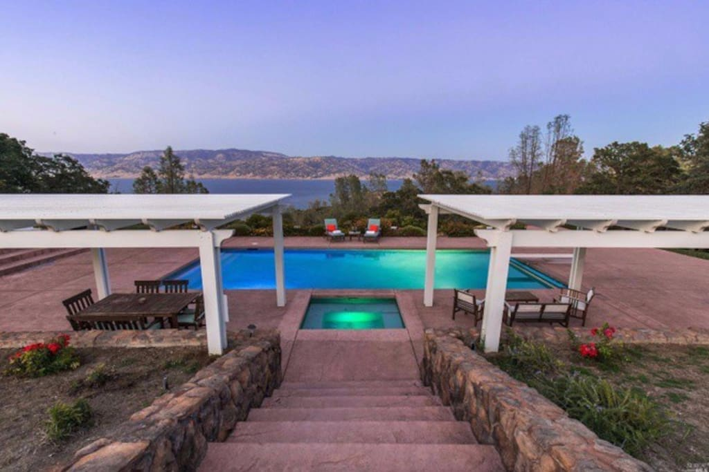 Expansive pool patio with hot tub overlooking the lake and mountains