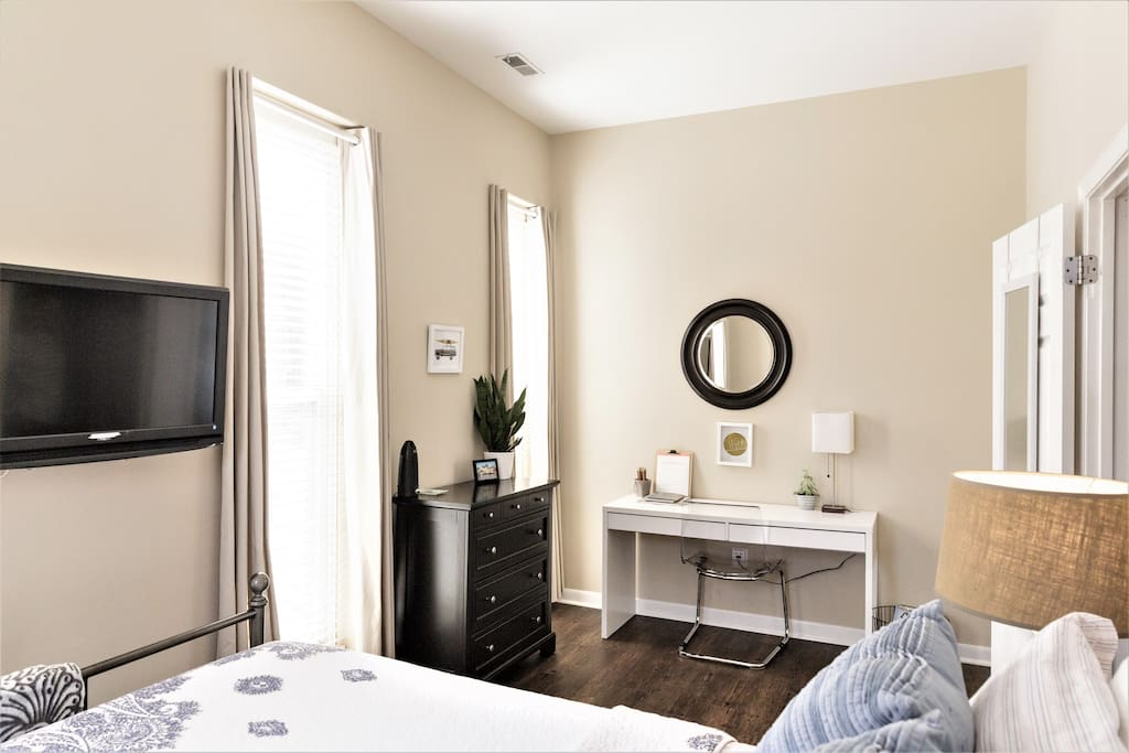 South Facing Sunny Bedroom with Queen Bed, Laptop Workspace, Dresser,  Luggage Rack, Blinds and Neutral Drapes.