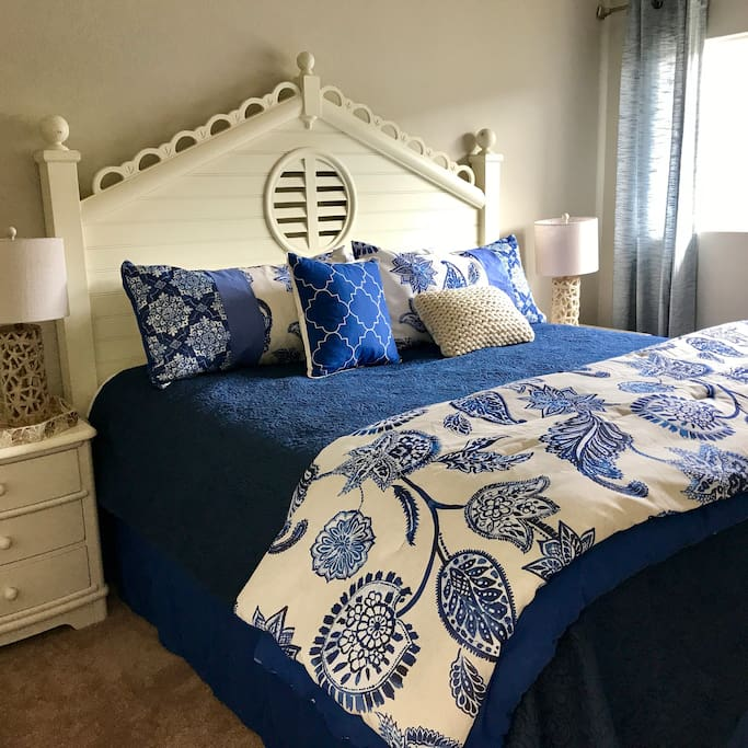 Master bedroom in nautical navy with a cape cod styled king bed