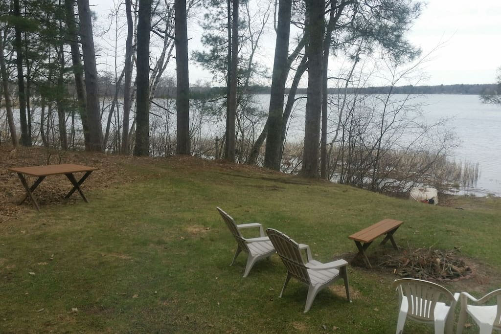 View of the lake with picnic table, chairs, porch swing and fire pit.