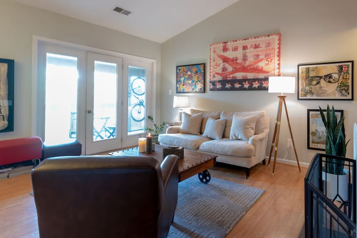 Living room with door to balcony and rear stairwell to parking space
