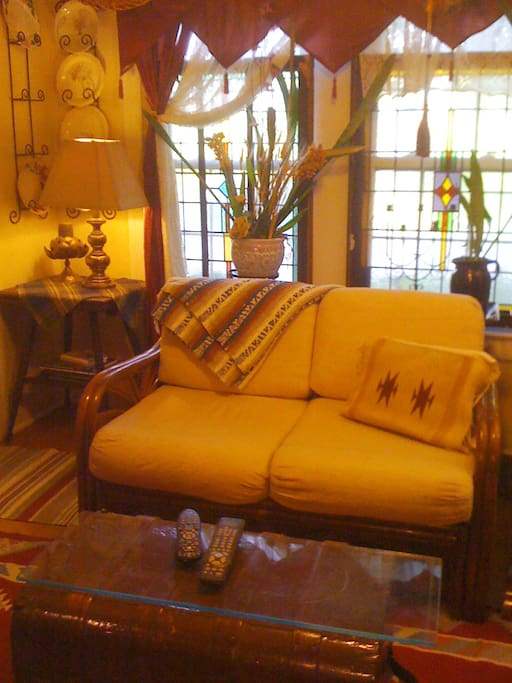 Living Room has stained glass windows.  Ratan couch is comfortable. Western Decor