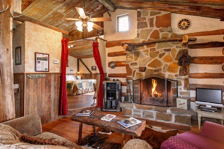 Living room with wood burning fireplace of Geneva Swiss Log Cabin
