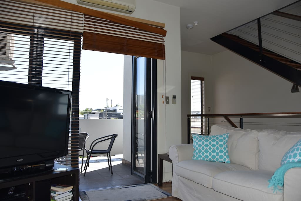Lounge with large TV & outdoor balcony with BBQ