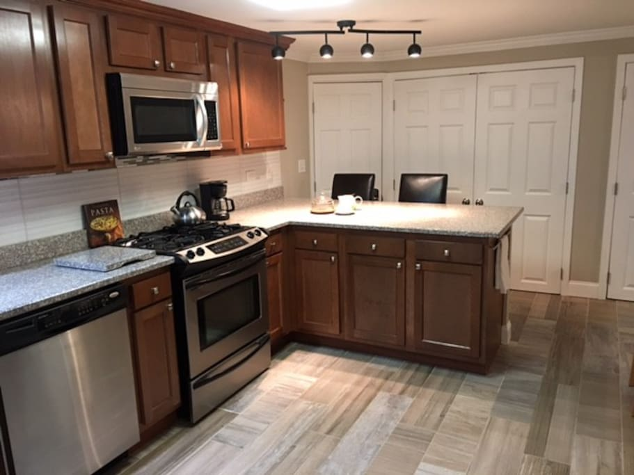 Full kitchen with granite countertops, oven, dishwasher, microwave and fridge with ice maker