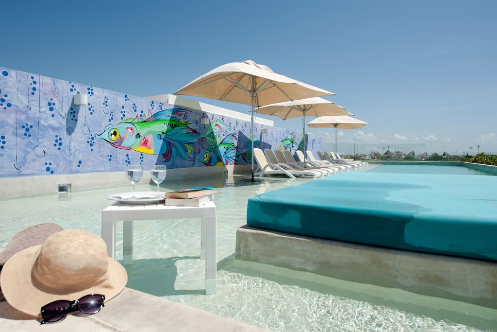 This is the pool on the roof top area, with incredible views of Playa del Carmen and even the sea, accessible by elevator, it has lounge chairs, umbrellas and beds in the water, the bottom Jacuzzi and bar area is shown.