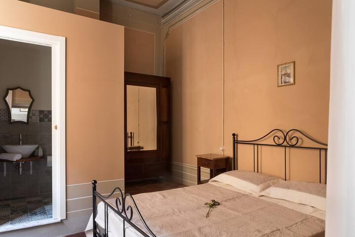 Camera in palazzo storico con giardino nascosto