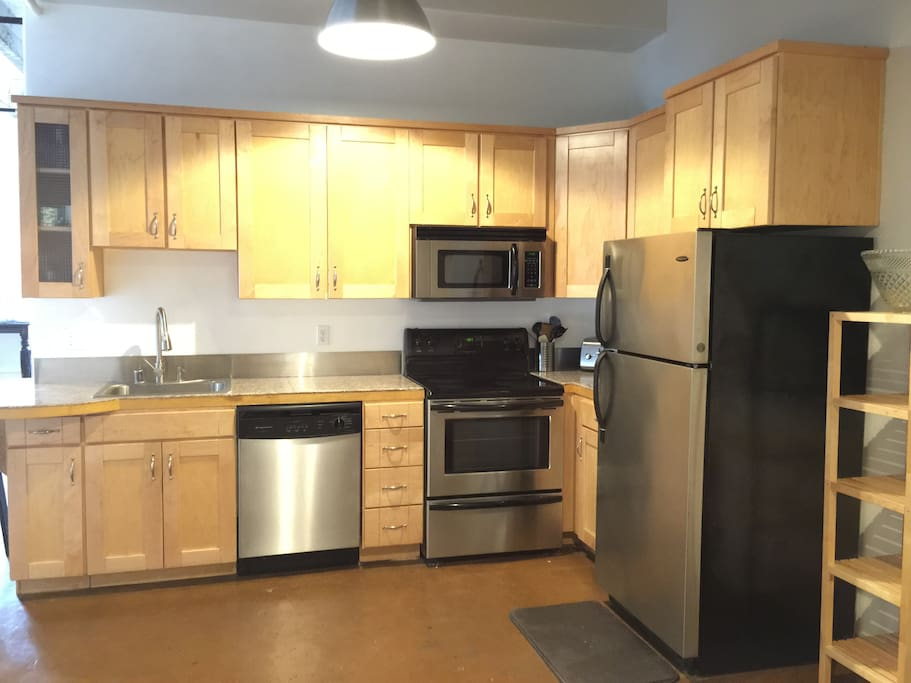 An open spacious kitchen with granite countertops and all the amenities.