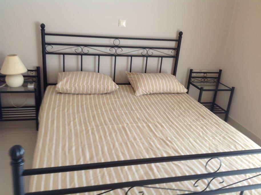 Chambre éclairée avec lit double et balcon