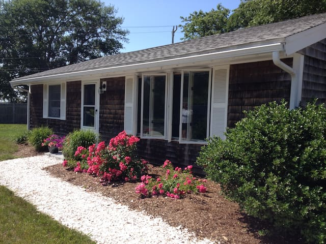 The front of house with roses in bloom and shell walkway.