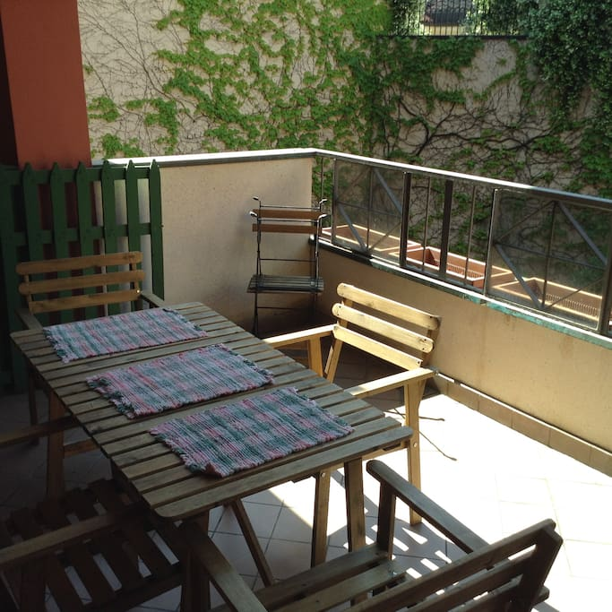 balcony with wooden table and 8 chairs.