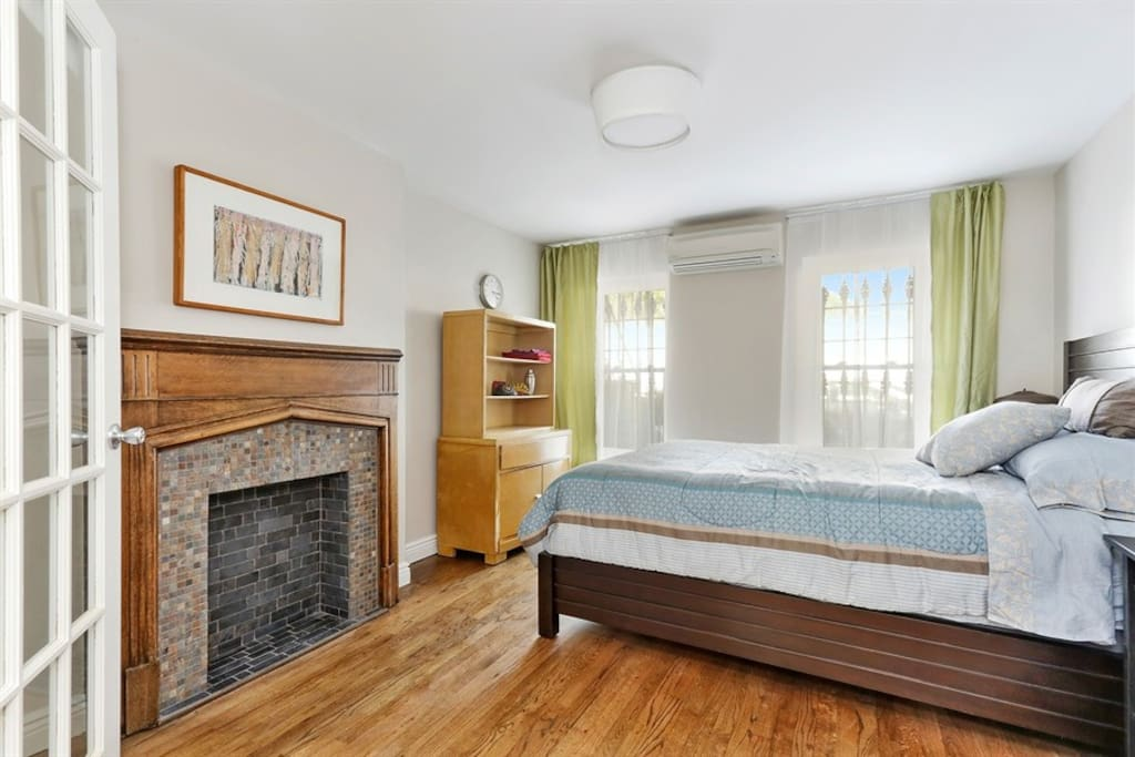 Big bedroom with nice bed with firm mattress & decorative fireplace.